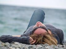 Señora joven en la reclinación de la playa Fotografía de archivo