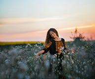 Señora joven en un vestido bordado en el prado en la puesta del sol Imagen de archivo
