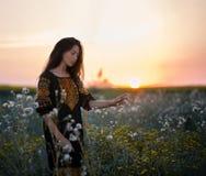 Señora joven en un vestido bordado en el prado en la puesta del sol Imágenes de archivo libres de regalías