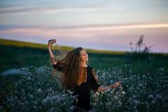 Señora joven en un vestido bordado en el prado en la puesta del sol Fotografía de archivo