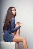 Señora joven en un vestido corto con las piernas desnudas, sentándose juguetónamente en una silla Imagen de archivo libre de regalías