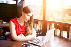 Señora joven en vestido rojo que hojea Internet Imagen de archivo