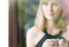 Señora joven encantadora en vestido negro y con la taza Imagenes de archivo