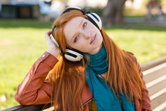 Señora joven encantadora relajada que disfruta de música en auriculares Imagen de archivo