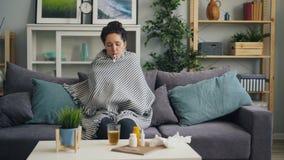 Señora joven enferma que comprueba temperatura con el termómetro en boca en el apartamento almacen de video