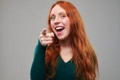 Señora joven entusiasta que señala en la cámara en el s Foto de archivo libre de regalías