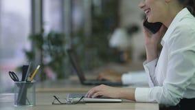 Señora joven feliz que recibe llamada de teléfono en la oficina, hablando con sonrisa en cara almacen de metraje de vídeo