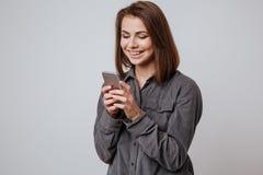 Señora joven feliz que usa el teléfono móvil Imágenes de archivo libres de regalías