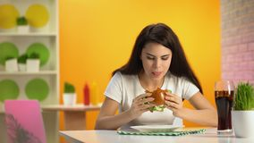 Señora joven hambrienta que come el cheeseburger sabroso en el café, vidrio del refresco en la tabla almacen de metraje de vídeo