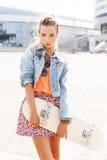Señora joven hermosa con un monopatín con la cubierta en blanco Imagen de archivo libre de regalías