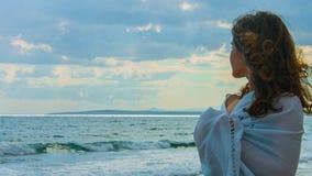 Señora joven hermosa en la playa que mira el horizonte, pensando en amor, romance almacen de metraje de vídeo