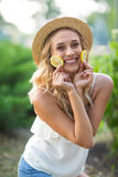 Señora joven hermosa en un fondo del parque Una hembra sonriente en un sombrero, sosteniendo los limones Dietas exóticas Forma de foto de archivo