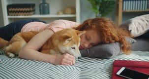 Señora joven hermosa que duerme en el sofá en casa que abraza el perrito adorable almacen de video