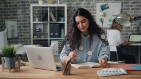 Señora joven hermosa que escribe en cuaderno y que trabaja con el ordenador portátil en oficina almacen de metraje de vídeo