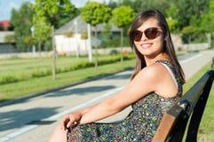 Señora joven hermosa que presenta en banco en parque Imagenes de archivo