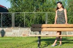 Señora joven hermosa que presenta en el parque que se coloca al lado de banco Imagenes de archivo