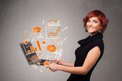 Señora hermosa que sostiene el cuaderno con los gráficos y las estadísticas imagenes de archivo