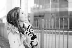 Señora joven hermosa que sostiene la cámara de la foto en el fondo de cristal del edificio de la ciudad Fotografía blanca negra Foto de archivo libre de regalías