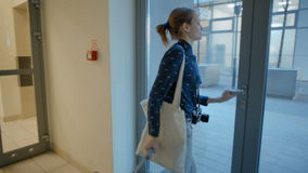 Señora joven Leaving Elevator y edificio a la calle con la maleta, el bolso y la cámara almacen de video
