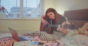 Señora joven linda que juega en una guitarra en su dormitorio, el llevar los pijamas ella pasa un buen rato consigo misma almacen de video
