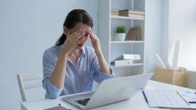 Señora joven pobre que lucha con dolor de cabeza en el trabajo