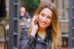Señora joven preciosa que sonríe y que mira lejos mientras que teniendo conversación del smartphone fotografía de archivo libre de regalías