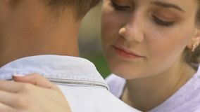 Señora joven que abraza al hombre, mirando la cámara, contracepción, anuncio social almacen de metraje de vídeo