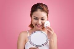 Señora joven que aplica colorete en su cara con el soplo de polvo y el MIR Fotos de archivo libres de regalías