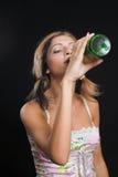 Señora joven que bebe de una botella de cerveza Imagenes de archivo