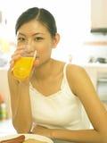 Señora joven que bebe su zumo de naranja Foto de archivo libre de regalías