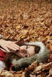Señora joven que bosteza en hojas Foto de archivo libre de regalías