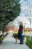 Señora joven que camina con su perro Mujer elegante del pelo rubio con el perro fornido foto de archivo libre de regalías
