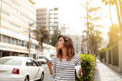 Señora joven que camina en la calle de la ciudad y que mira lejos Imágenes de archivo libres de regalías