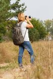 Señora joven que camina en un camino rural con la cámara digital Imagenes de archivo