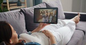 Señora joven que charla con los amigos en línea que hacen la llamada video con la tableta en casa almacen de metraje de vídeo