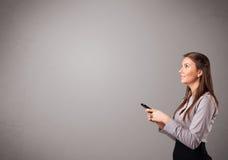 Señora joven que coloca y que sostiene un teléfono con el espacio de la copia Imágenes de archivo libres de regalías