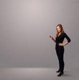 Señora joven que coloca y que sostiene un teléfono con el espacio de la copia Foto de archivo libre de regalías