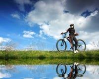 Señora joven que completa un ciclo cerca del lago Fotografía de archivo libre de regalías