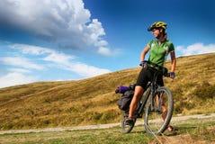 Señora joven que completa un ciclo en las montañas Fotografía de archivo libre de regalías