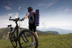 Señora joven que completa un ciclo en las montañas Fotos de archivo