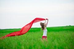 Señora joven que corre con el tejido en campo verde Mujer con la bufanda Imagen de archivo libre de regalías