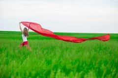 Señora joven que corre con el tejido en campo verde Mujer con la bufanda Imagen de archivo