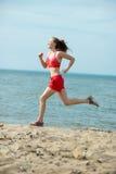 Señora joven que corre en la playa soleada de la arena del verano entrenamiento sacudida foto de archivo