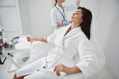 Señora joven que descansa mientras que doctor que regula el goteo intravenoso foto de archivo libre de regalías
