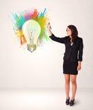 Señora joven que dibuja una bombilla colorida Imagen de archivo libre de regalías