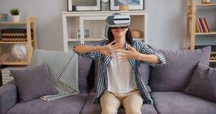 Señora joven que disfruta de nueva experiencia en los vidrios aumentados de la realidad que se sientan en el sofá almacen de video