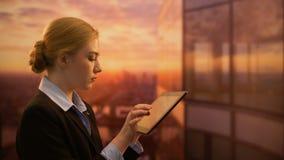 Señora joven que elige viaje en Internet, mirando puesta del sol y soñando con vacaciones almacen de metraje de vídeo
