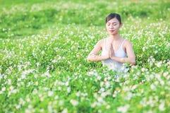 Señora joven que hace ejercicio de la yoga en campo verde con la pequeña área al aire libre de las flores blancas que muestra la  imagen de archivo libre de regalías