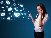 Señora joven que hace llamada de teléfono con los iconos del mensaje Imágenes de archivo libres de regalías