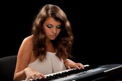 Señora joven que juega el piano Fotos de archivo